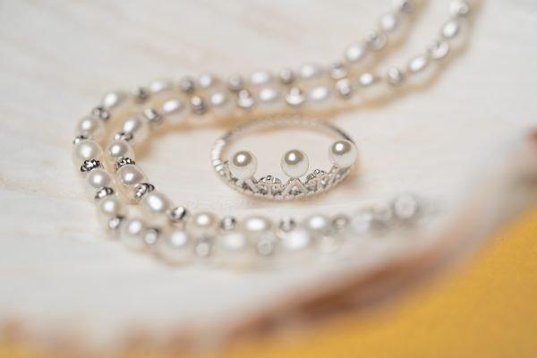 кадър на фокус със сребърен пръстен под формата на корона и три перли