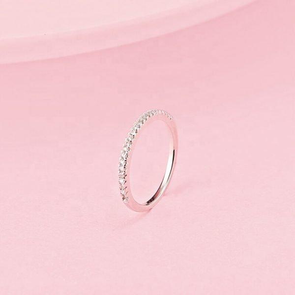 сребърен пръстен тип халка с малки циркони сниман на розов фон