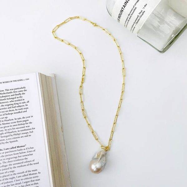 gold plated silver necklace with a large baroque pearl photographed on a white surface between a book and a glass bottle