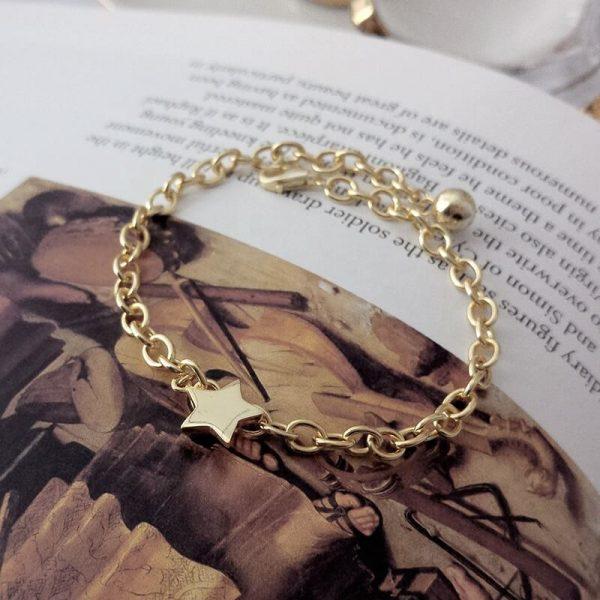масивна сребърна гривна със златно покритие и звездовиден елемент снимана върху страница от книга