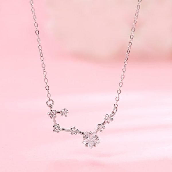 frontal close-up of silver necklace with delicate zircon pendant in the form of stars on pink background