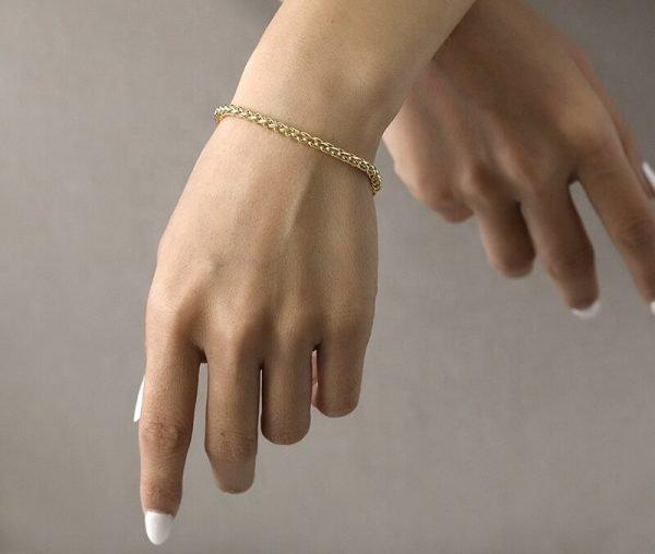дамска ръка с масивна позлатена гривна от плетка тип житен клас