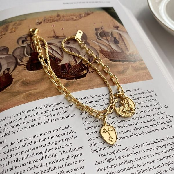 solid silver bracelet with 18-carat gold plating and two types of braids photographed on a page from a book