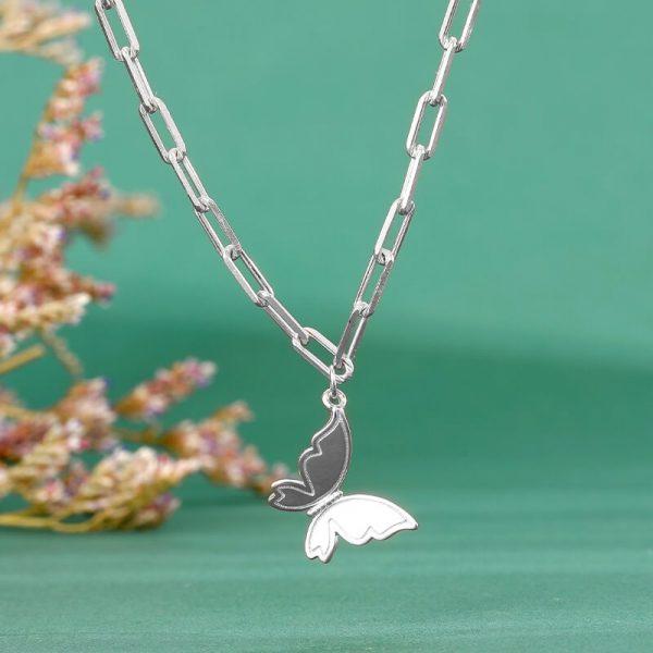 сребърно колие тип чоукър с медальон под формата на пеперуда снимано в детайл на зелен фон