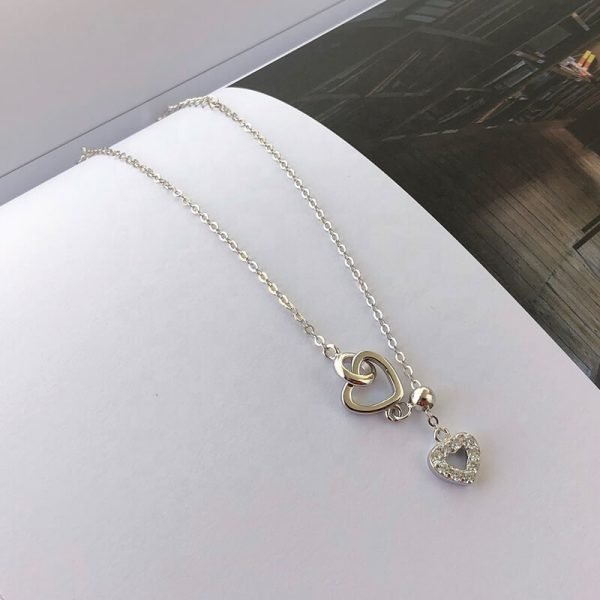silver bracelet with heart-shaped pendants and hanging chain lowered on a book page