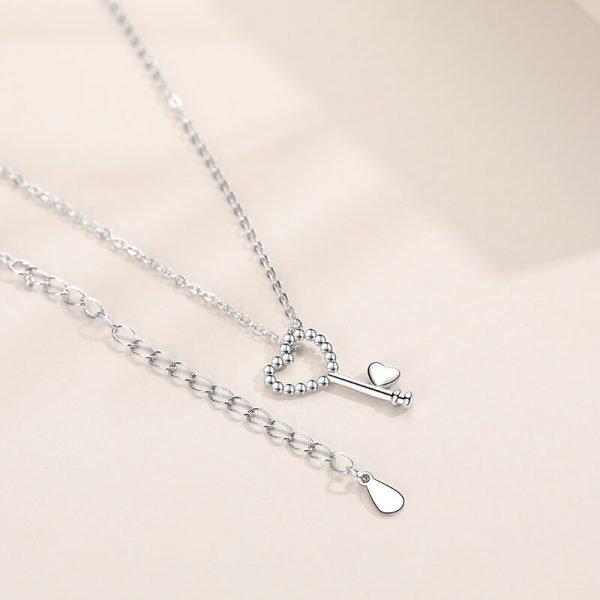сребърно колие с медальон под формата на сърцевиден ключ снимано върху светла повърхност