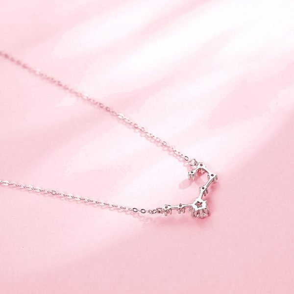 the back of a silver necklace with a delicate star-shaped zircon pendant photographed at an angle against a pink background