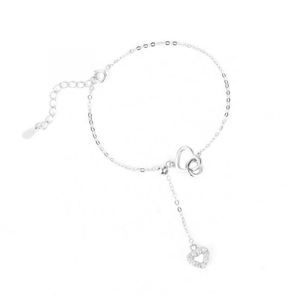 silver bracelet with heart-shaped medallions and hanging chain on white background