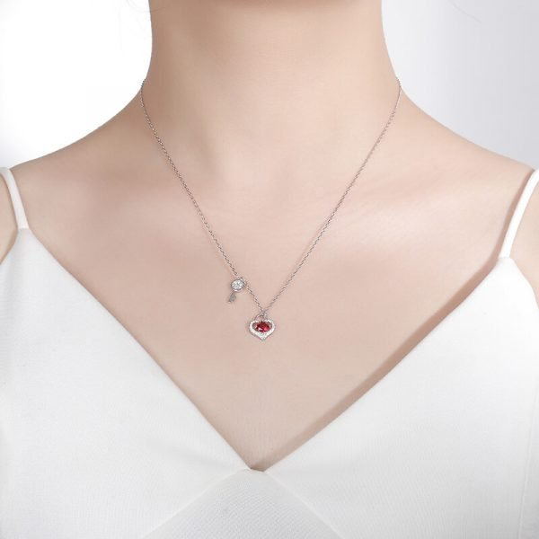 a woman with a white tank top and a silver necklace with two pendants - a key and a heart with a red crystal
