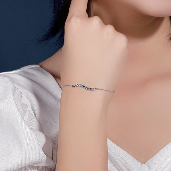 ladies model with delicate silver bracelet with multicolored cubic zircons