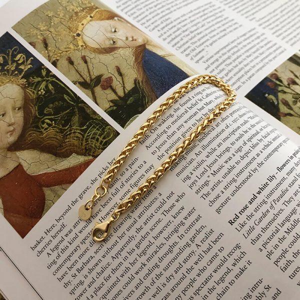 масивна позлатена гривна от плетка тип житен клас снимана разкопчана върху страница от книга