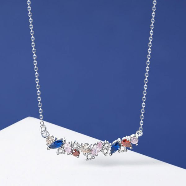 frontal shot of a delicate silver necklace with multicolored cubic zircon on a dream-white background