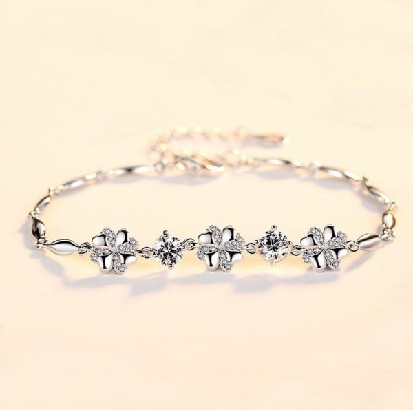 frontal focus photo with silver bracelet with three flowers and round cubic zircons between them
