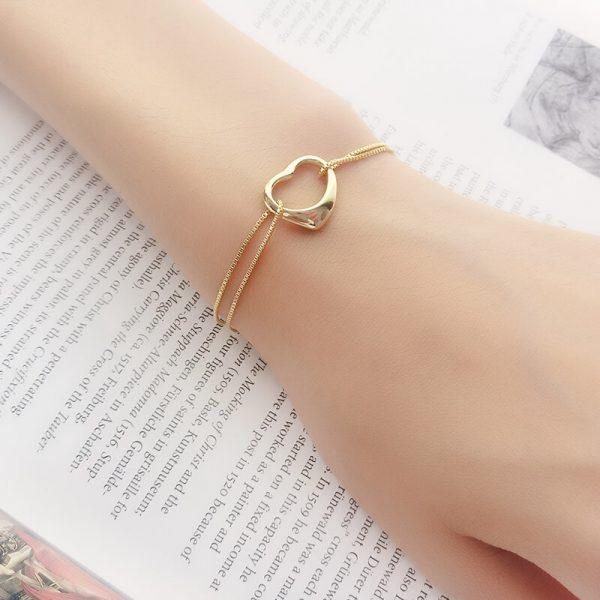 двойна сребърна гривна със златно покритие и сърцевиден елемент в средата на женска ръка