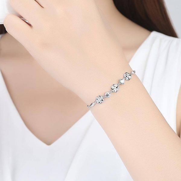 a woman with a white blouse and a silver bracelet with three flowers and round cubic zircons between them