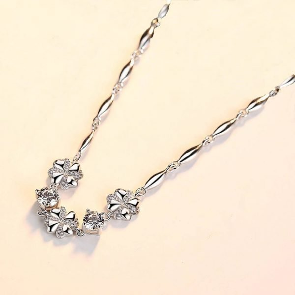 silver bracelet with three flowers and round cubic zircons between them