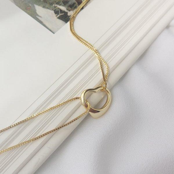двойна сребърна гривна със златно покритие и сърцевиден елемент в средата снимана под лек ъгъл върху ръба на книга