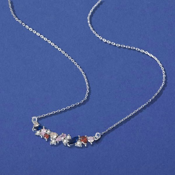 delicate silver necklace with multicolored cubic zirconia photographed from above on a blue surface