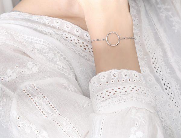 дамски модел с бяла буза и нежна сребърна гривна с кръгъл елемент