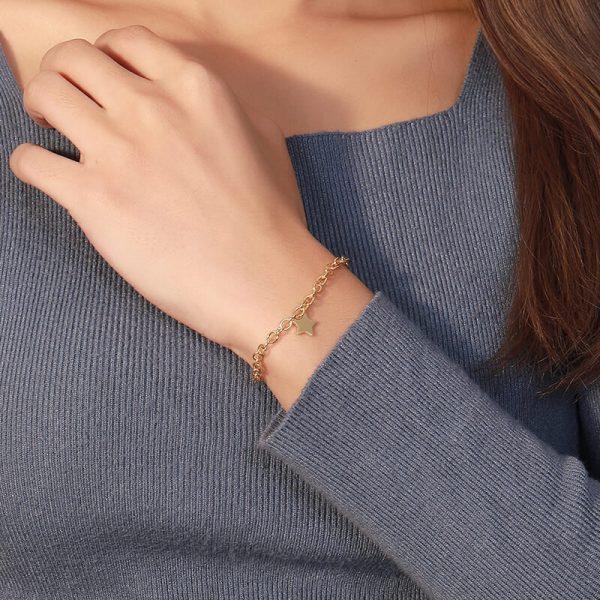 дамски модел носещ масивна сребърна гривна със златно покритие и звездовиден елемент