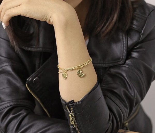 woman with a leather jacket and a massive silver bracelet with 18-carat gold plating and two types of braids