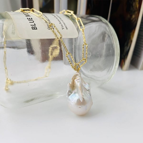 gold plated silver necklace with a large baroque pearl photographed on a glass bottle
