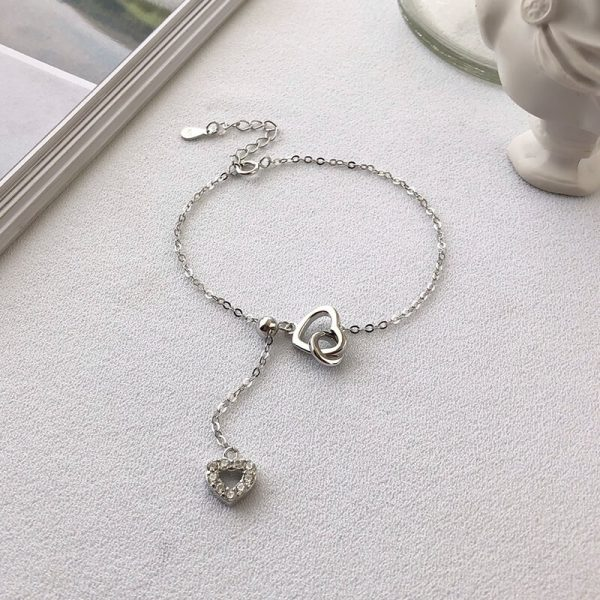 silver bracelet with heart-shaped medallions and hanging chain photographed on white surface