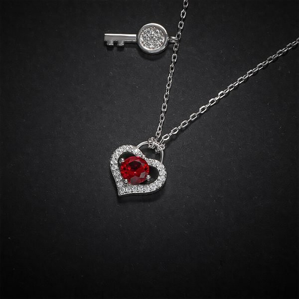 silver necklace with two pendants - key and heart with red crystal photographed on black surface