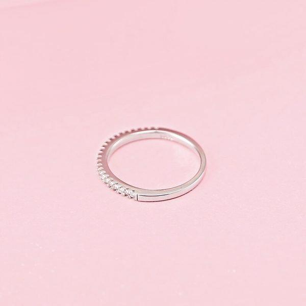 сребърен пръстен тип халка с малки циркони сниман легнал върху розов фон