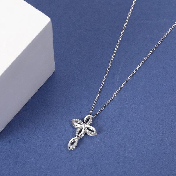 сребърно колие с два медальона под формата на кръст с нежни извивки върху синя повърхност