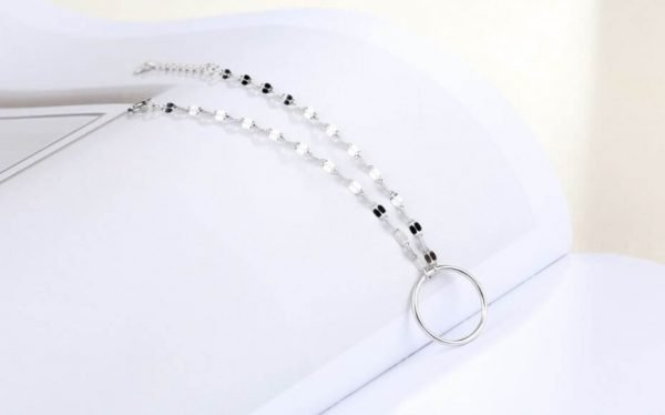 нежна сребърна гривна с кръгъл елемент спусната върху бяла повърхност