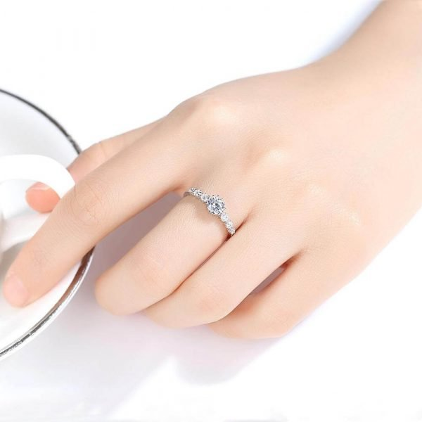 ladies hand with a silver ring with a massive cubic zirconia and three smaller stones on each side