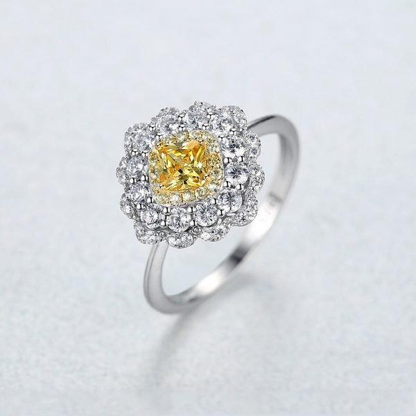 дамска ръка със сребърен пръстен с масивен жълт кристал и малки камъчета около него сниман под лек ъгъл на бял фон