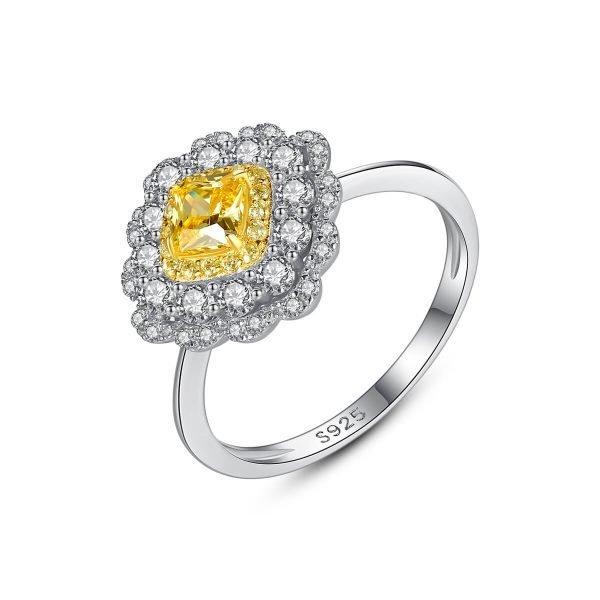 детайлна снимка на бял фон със дамска ръка със сребърен пръстен с масивен жълт кристал и малки камъчета около него сниман под лек ъгъл на бял фон