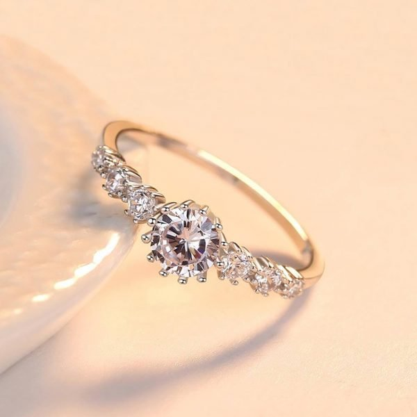 silver ring with massive cubic zirconia and three smaller stones on each side set at a slight angle on a ceramic vessel
