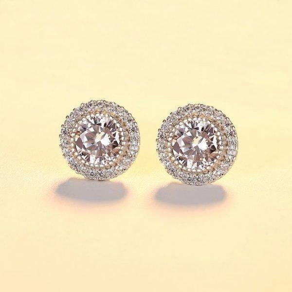 кръгли сребърни обеци масивен цирконий и малки камъни около него снимани фронтално на светъл фон