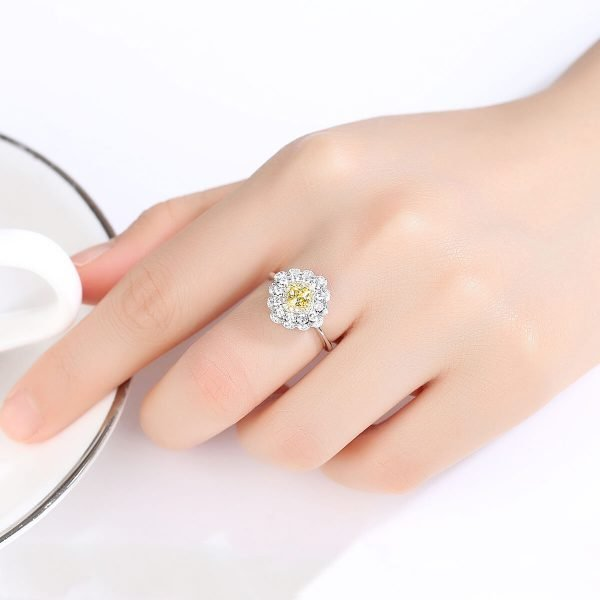 дамска ръка със сребърен пръстен с масивен жълт кристал и малки камъчета около него