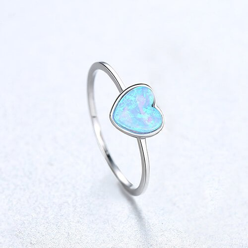 delicate silver ring with blue synthetic opal in the shape of a heart photographed from above
