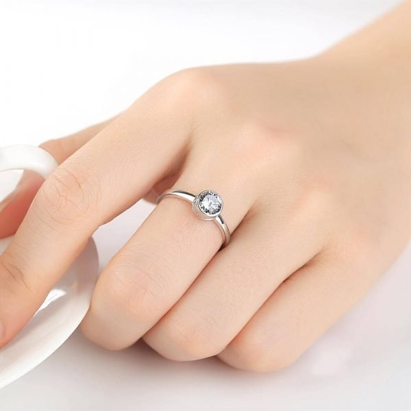 woman's hand with clear silver ring with round cubic zirconia
