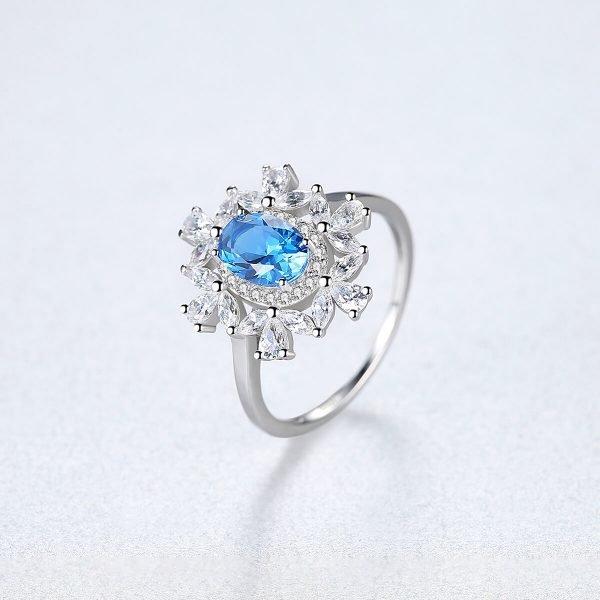 сребърен пръстен с малки циркони и масивен син топаз в центъра сниман под лек ъгъл на светъл фон