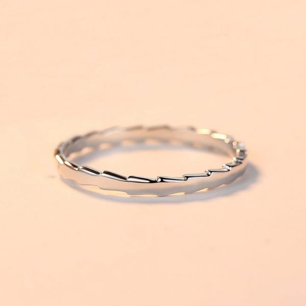 clean silver ring with a jagged shape photographed in focus lying down