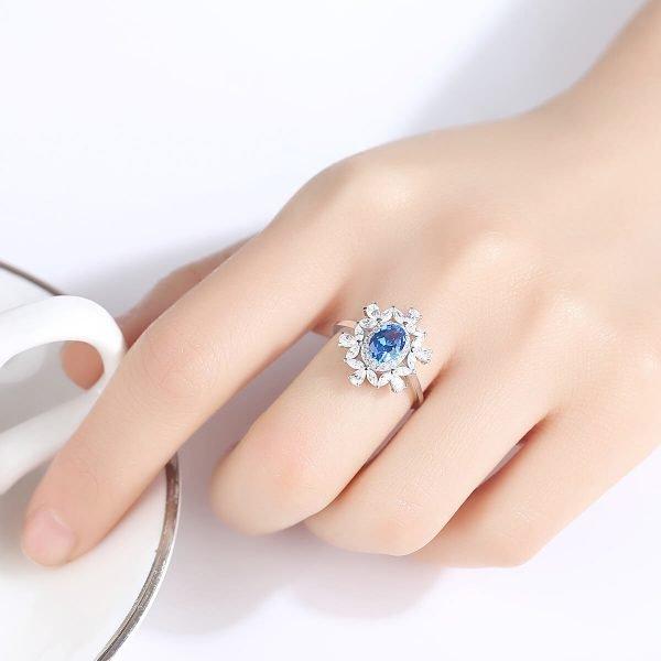дамска ръка със сребърен пръстен с малки циркони и масивен син топаз в центъра