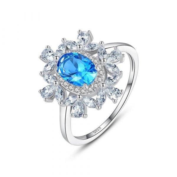 сребърен пръстен с малки циркони и масивен син топаз в центъра сниман на бял фон