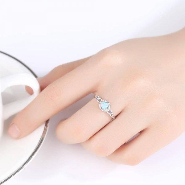 дамска ръка със сребърен пръстен с кръгъл синтетичен опал опал в центъра