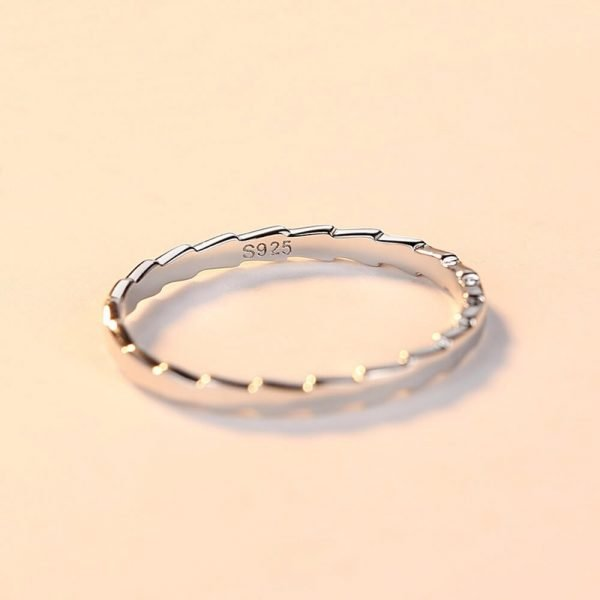 clean silver ring with a jagged shape placed lying on a bright surface - focus on the 925 seal