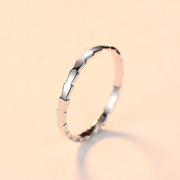 clean silver ring with jagged shape photographed at a slight angle against a light background