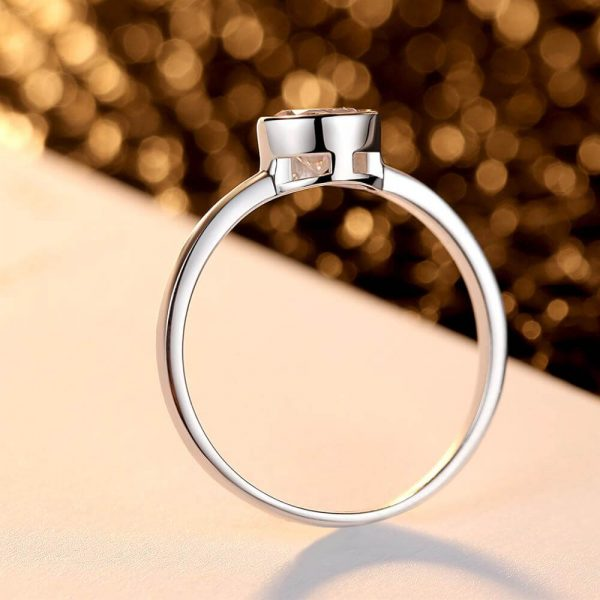clean silver ring with round cubic zirconia photographed on the side with focus on the ring band