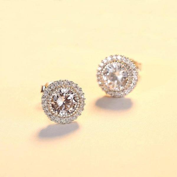кръгли сребърни обеци с множество малки камъни и масивен цирконий снимани на светложълт фон