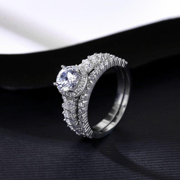 двоен сребърен пръстен с множество малки циркони и един по-масивен камък сниман под ъгъл на черно-бял фон