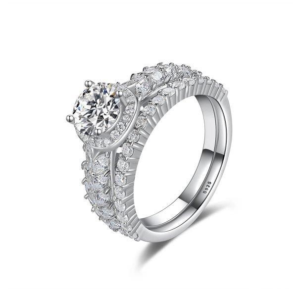 двоен сребърен пръстен с множество малки циркони и един по-масивен камък сниман под ъгъл на бял фон